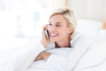 Smiling blonde woman lying on the bed and calling on the phone in her bedroom Royalty Free Stock Photography