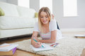 Smiling blonde woman lying on floor sketching on paper in living room Royalty Free Stock Image