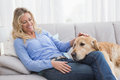 Smiling blonde woman petting her golden retriever Royalty Free Stock Photo