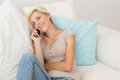 Smiling blonde woman phoning on the sofa Royalty Free Stock Photo
