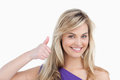 Smiling blonde woman placing her thumbs up Royalty Free Stock Photo
