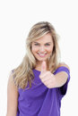 Smiling blonde woman placing her thumbs up in agreement Stock Photo