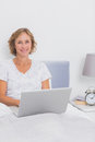 Smiling blonde woman sitting in bed using laptop looking at camera at home bedroom Stock Image