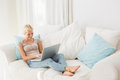 Smiling blonde woman using her laptop in the sofa