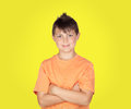 Smiling boy with arms crossed on yellow background Royalty Free Stock Image