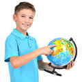 Smiling boy in casual holding globe with hands and points on it isolated on white Royalty Free Stock Photography