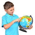 Smiling boy in casual holding globe with hands and points on it isolated on white Royalty Free Stock Photo