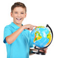 Smiling boy in casual holding globe with hands and points on it isolated on white Royalty Free Stock Image