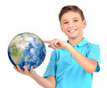 Smiling boy in casual holding planet earth in hands and points on it isolated on white Royalty Free Stock Image