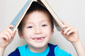 Smiling boy with dropped milk tooth with book on head making roo Royalty Free Stock Photo