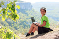 Smiling boy in green t shirt with a netbook on top of the mounta happy caucasian and cap mountain Royalty Free Stock Photography