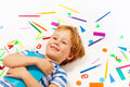 Smiling boy having a rest among heap of stationery Royalty Free Stock Photo