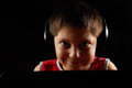 Smiling boy in headphones behind laptop closeup photo Stock Photos
