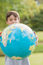 Smiling boy holding an earth globe in the park Royalty Free Stock Photo
