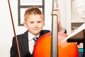 Smiling boy holding fiddlestick, play violoncello Royalty Free Stock Photo