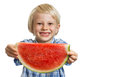 Smiling boy holding out slice of water melon a a big juicy watermelon isolated on white Stock Images