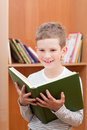 Smiling boy holds big green book against bookcase Royalty Free Stock Photo