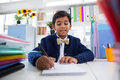 Smiling boy imitating as businessman writing on paper Royalty Free Stock Photo