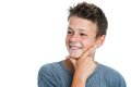 Smiling boy looking aside close up portrait of cute teen with hand on chin isolated on white background Royalty Free Stock Image