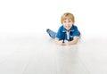 Smiling boy lying on white floor Royalty Free Stock Photo