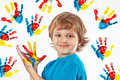 Smiling boy with painted hands on background of hand prints a Royalty Free Stock Photo