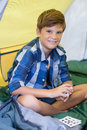 Smiling boy playing cards while sitting in tent Royalty Free Stock Photo