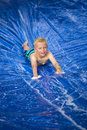 Smiling boy playing on a slip and slide outdoors Royalty Free Stock Photo