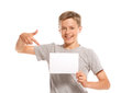 Smiling boy pointing at white blank paper isolated on background Stock Photo