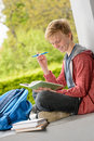 Smiling boy reading book sitting outside school teenage on wall Stock Photography