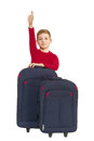 Smiling boy showing thumbs up with travel bags isolated on white Stock Images