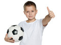 Smiling boy with soccer ball a holds his thumb up on the white background Royalty Free Stock Image