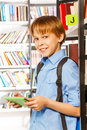Smiling boy stands and holds books in library near bookshelf Stock Image
