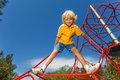 Smiling boy stands on red rope with legs apart and holds one arm Royalty Free Stock Photo