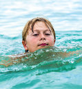 Smiling boy swimming in the ocean happy enjoys Stock Images