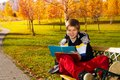 Smiling boy with textbook years old sitting on the bench in autumn park smile on the on his face and reading from Stock Images