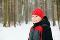 Smiling boy in winter forest wearing red hat and gray jacket standing Royalty Free Stock Images