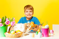 Smiling boys holds plate with eastern eggs on and rabbit sitting on the table the yellow background Royalty Free Stock Photos