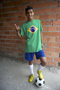 Smiling brazilian teen thumbs up with football soccer ball wearing flag t shirt standing by rustic favela wall giving Royalty Free Stock Images