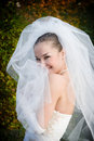 A smiling bride hides into her veil Royalty Free Stock Photos