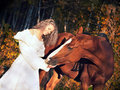Smiling bride  with horse in forest at evening Royalty Free Stock Photo