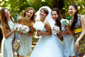 Smiling bride poses with happy bridesmaids with bouqets in their Royalty Free Stock Photo