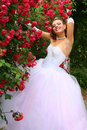 Smiling Bride in the Red Roses Stock Photos