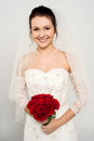 Smiling bride with a rose bouquet gorgeous young against gray Stock Photography