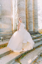 Smiling bride is spinning in the pompous wedding dress standing on the stair of the old antique building. Royalty Free Stock Photo