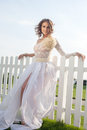 Smiling bride standing near white fence Royalty Free Stock Photo