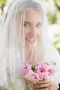 Smiling bride wearing veil over face holding bouquet looking at camera in the countryside Royalty Free Stock Photography