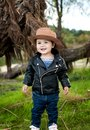 A smiling brown-eyed little girl wears a cowboy hat, a leather j Royalty Free Stock Photo