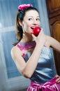 Smiling brunette girl eating red juicy apple