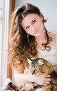 Smiling brunette girl and her cat over beautiful ginger Stock Image