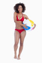 Smiling brunette holding a beach ball while standing upright Royalty Free Stock Images